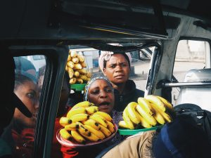 person standing near vehicle holding banana fruits