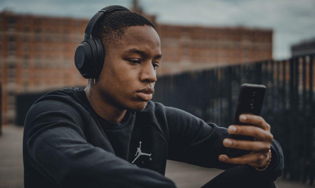 man in black nike hoodie wearing black headphones